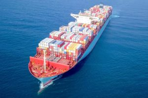 Ultra large container vessel (ULCV 366 Meters long) loaded with various Container brands, at sea - Aerial image.